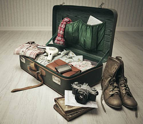 Vintage suitcase open on a wood floor in an empty room